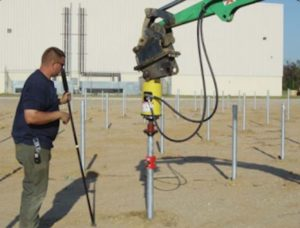 Man watching ECP One Step Foundation System helical pile solar panel foundation.