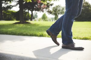 Blue jean wearing legs with brown shoes walking on sidewalk with green grass and a tree in the background.