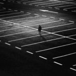 Empty parking lot at night with a single light illuminating a solitary figure