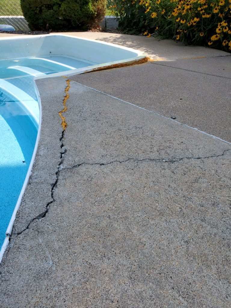 Edge of swimming pool with a giant crack running along the pool deck.