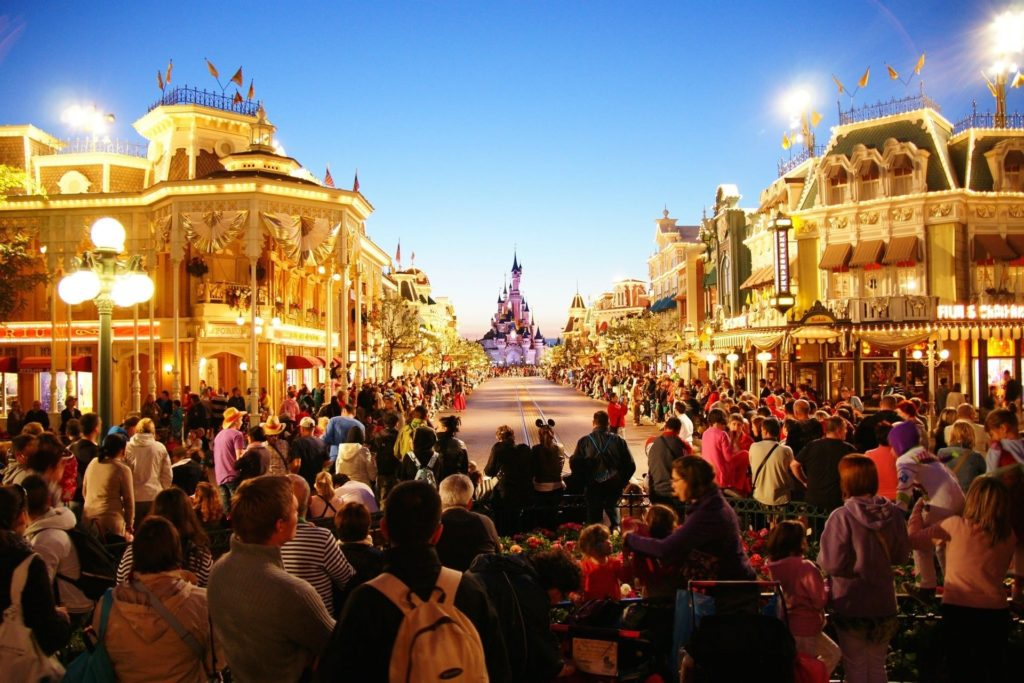 Disney Main Street U.S.A. with a crowd of people looking toward castle.