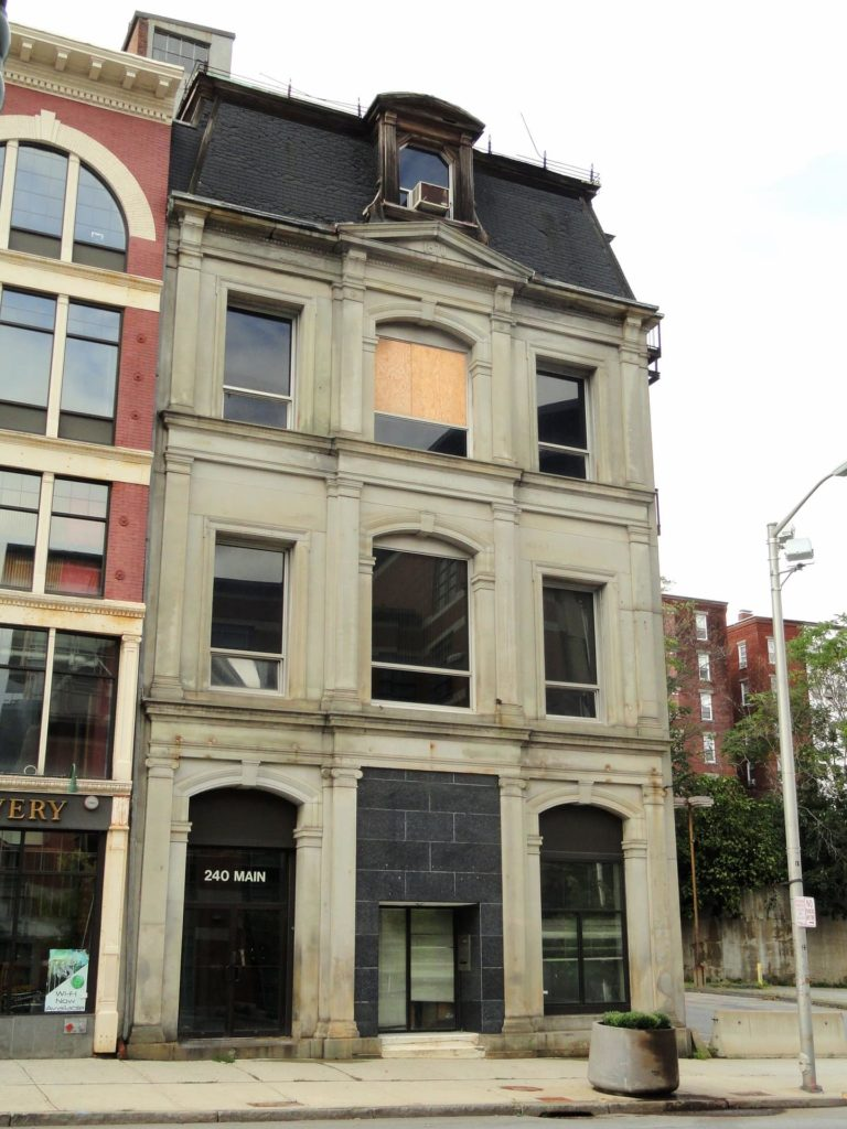 Four-story downtown building with a boarded upper window.